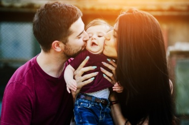 father-mother-kissing-baby-cheeks_1153-2054